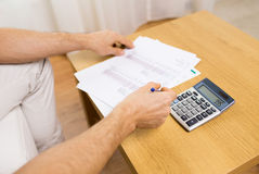 Close up of man with papers and calculator at home Royalty Free Stock Photo