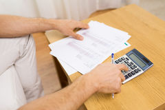 Close up of man with papers and calculator at home Royalty Free Stock Photography