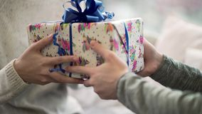 Close-up of man passes gift to woman. Close-up guy gave his girlfriend Christmas or new year`s gift. Festive winter stock video footage