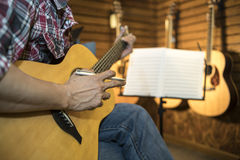 Close up of a man playing acoustic guitar. Royalty Free Stock Photography