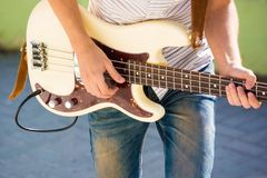 Close up of man playing bass guitar outdoors Stock Photo