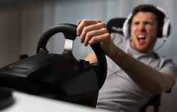 Close up of man playing car racing video game. Technology, gaming, entertainment, let's play and people concept - close up of angry young man in headphones with royalty free stock image