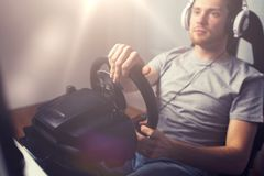 Close up of man playing car racing video game. Technology, gaming, entertainment, let`s play and people concept - close up of young man in headphones with pc stock photo