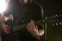 Close Up Of Man Playing Electric Guitar In Studio Stock Photos