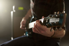 Close Up Of Man Playing Electric Guitar In Studio royalty free stock image