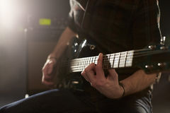 Close Up Of Man Playing Electric Guitar In Studio Stock Photo