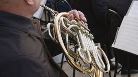 Close up man playing on french horn on city street. Street musician play music on wind instrument. Outdoor performance