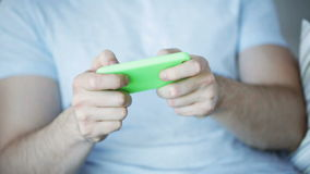 Close up of man playing game on smartphone at home stock video footage
