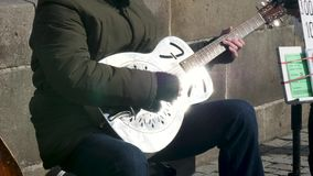 Close up of a man playing a guitar as part of a street band stock video footage