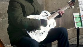 Close up of a man playing a guitar as part of a street band stock video