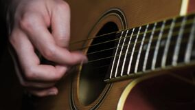 Close-up of man playing guitar. Concept. Professional guitar player moves fingers along strings of guitar beautifully