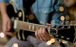 Close up of man playing guitar at studio rehearsal Royalty Free Stock Image