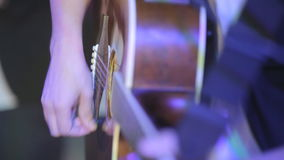 Close-up of the man playing the quitar in the