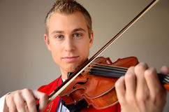 Close-up of a man playing violin. Close-up of a young blonde man in folkloric costume playing violin Royalty Free Stock Photography