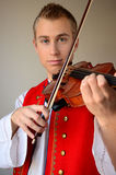 Close-up of a man playing violin. Young blond man in folkloric costume playing violin Royalty Free Stock Photo