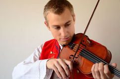 Close-up of a man playing violin. Young blond man in folkloric costume playing violin Stock Photos