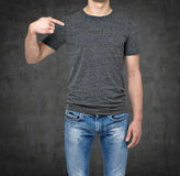 Close-up of a man pointing his finger on a blank grey t-shirt. Royalty Free Stock Image