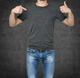 Close-up of a man pointing his finger on a blank grey t-shirt, other hand the thumb up. Stock Photo