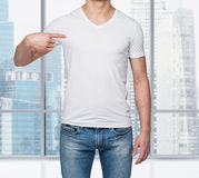 Close-up of a man pointing his finger on a blank t-shirt. Royalty Free Stock Image
