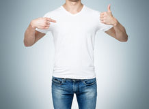 Close-up of a man pointing his finger to a blank t-shirt, and the thumb up. Royalty Free Stock Images