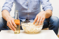 Close up of man with popcorn and beer at home Royalty Free Stock Photography