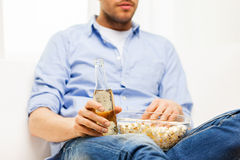 Close up of man with popcorn and beer at home Stock Photo