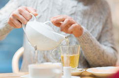 Close up of man with pot pouring tea at cafe royalty free stock image
