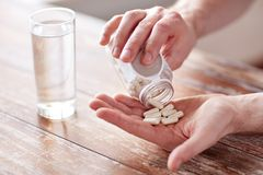 Close up of man pouring pills from jar to hand. Sport, healthy lifestyle, medicine, nutritional supplements and people concept - close up of man in fitness Stock Photography