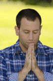 Close up of man praying outdoors. Royalty Free Stock Photo