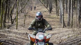 Close up of a man in protective equipment and helmet operating ATV and moving along the road from side to side. Fan of stock footage
