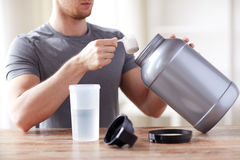 Close up of man with protein shake bottle and jar Royalty Free Stock Photography