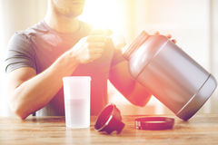 Close up of man with protein shake bottle and jar Royalty Free Stock Photos