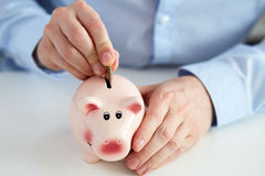 Close up of a man putting coin into piggy bank Stock Photo