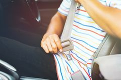 Man putting on his seat belt in his car. Safety drive concept. Close up Man putting on his seat belt in his car. Safety drive concept royalty free stock photos