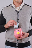Close up of man putting money into piggy bank. Savings Account in Euros Stock Photo