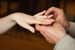 Close up on man putting on ring during marriage proposal Royalty Free Stock Photos