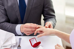 Close up of man putting ring to his fiance finger. Couple, love, engagement and holiday concept - close up of men putting ring to his fiance finger at restaurant Royalty Free Stock Photos
