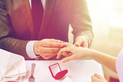 Close up of man putting ring to his fiance finger. Couple, love, engagement and holiday concept - close up of men putting ring to his fiance finger at restaurant Royalty Free Stock Images