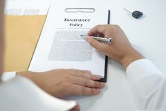 Close-up man reading insurance policy, contract with car key on table stock photos