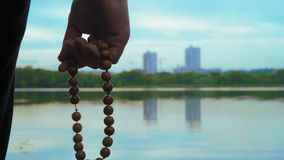 Close-up, Man Reads Mantra Holding Rosary in Hand on River Bank. Close-up, Man Reads Mantra Holding Wooden Rosary in His Hand on the River Bank stock footage