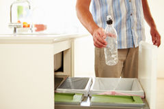 Close Up Of Man Recycling Kitchen Waste In Bin. Holding Plastic Bottle Royalty Free Stock Images