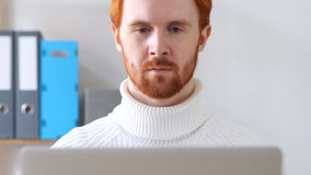 Close-up of  Man with Red Hairs and Beard Working on Laptop Royalty Free Stock Image