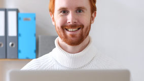 Close-up of  Man with Red Hairs Smiling at Work. High quality Stock Photos
