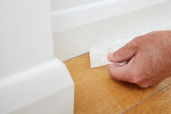 Close Up Of Man Removing Masking Tape From Skirting Board stock photography