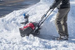Man Removing Snow with a Snowblower on a Sunny Day. Close Up of a Man Removing Snow with a Snowblower on a Sunny Day Stock Photo