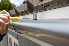 Close Up Of Man Replacing Guttering On Exterior Of House Stock Image