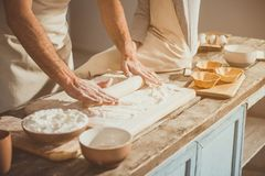 Male person unrolling soft dough. Close up of man rolling out mild batter on processing board. Boy sitting on table Royalty Free Stock Images