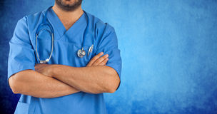 Close up of a man's arms crossed of medical staff. On blue background Royalty Free Stock Photos