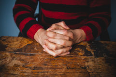 Close up on a man's clasped hands at a table Stock Photography