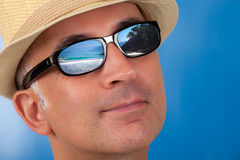 Close up of a man's face wearing sunglasses. With a beach reflection Royalty Free Stock Photo